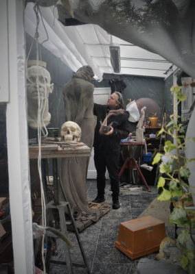 An artist in his studio, making a clay statue.