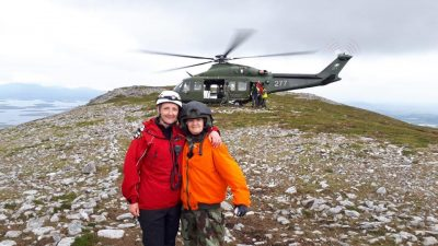 Two women on a mountain, standing in front of a helicopter